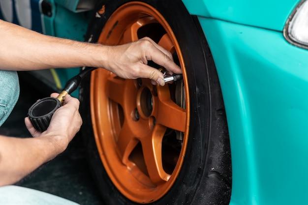 Mãos do homem mecânico que verificam a pressão de ar do pneu.