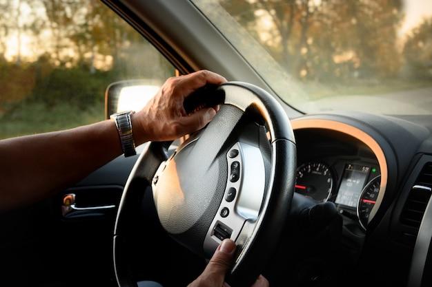 Mãos do homem no volante do carro de viagem de verão em direção ao pôr do sol