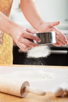 Mãos do homem peneirando farinha em uma peneira para assar