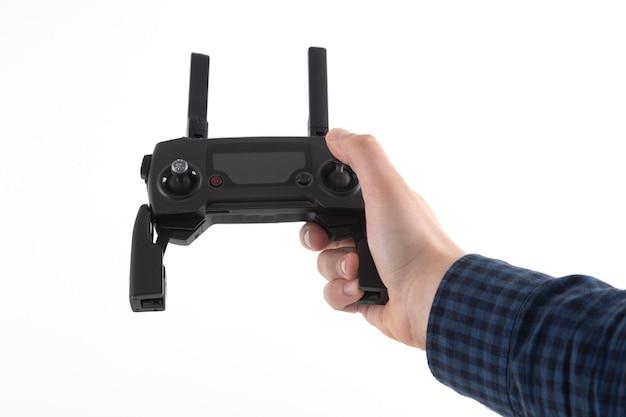 Mãos do homem que segura o controle remoto do quadricóptero em um branco