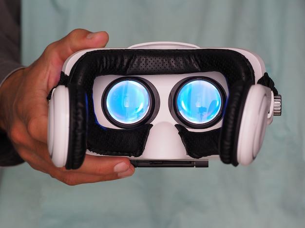 Mãos do homem segurando óculos de realidade virtual. luz azul por dentro.