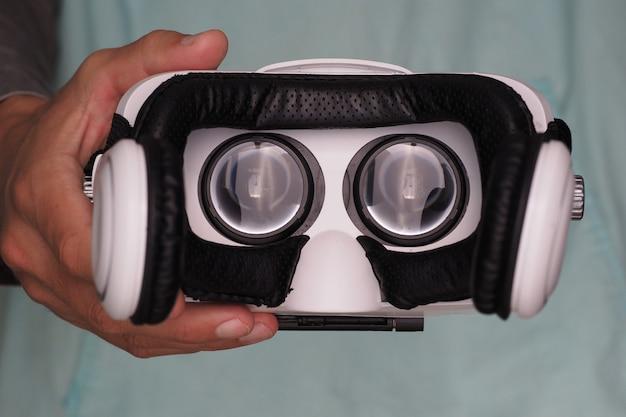 Mãos do homem segurando óculos de realidade virtual.