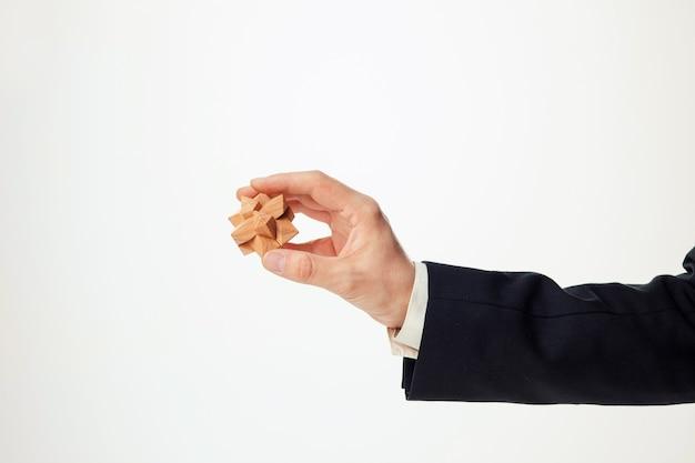 Mãos do homem segurando um quebra-cabeça de madeira.