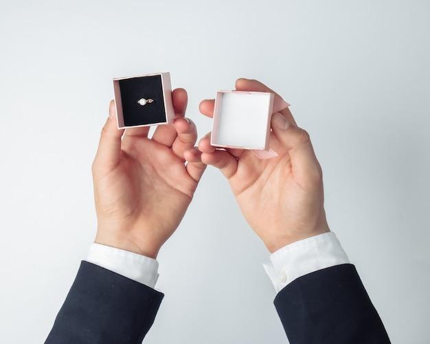 Mãos do homem segurando uma caixa de presente com um anel de diamante dourado em um branco