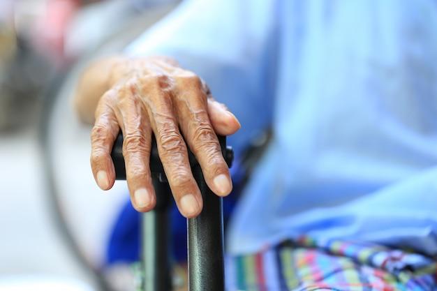 Mãos do homem sênior, sentado no banco em casa