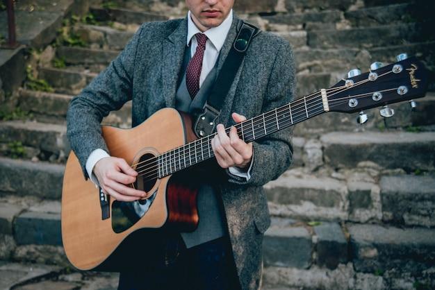 Mãos do homem tocando violão. fundo autêntico.