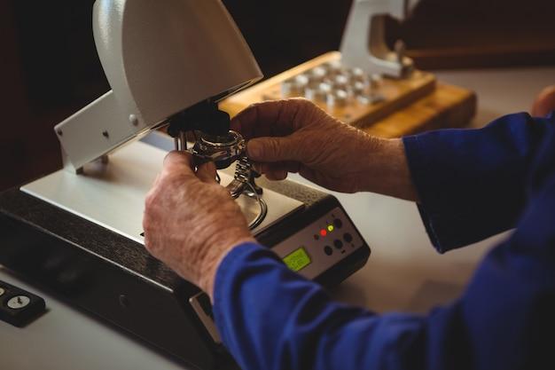 Mãos do horólogo reparando um relógio