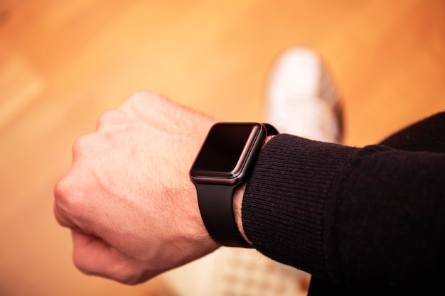 Mãos do indivíduo negro africano que veste o relógio esperto na moda.