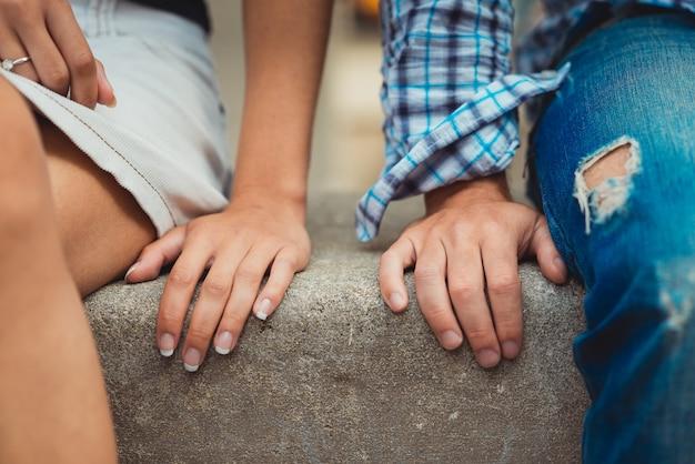Mãos do jovem casal apaixonado fecham lado a lado no primeiro encontro