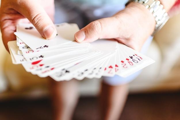 Mãos do mágico que fazem o truque de mágica com cartões de jogo.
