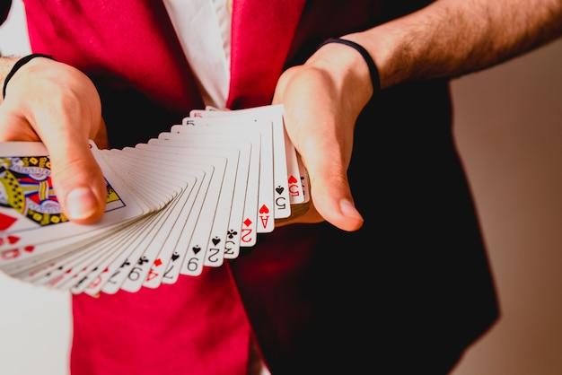 Mãos do mágico que fazem truques com um baralho de cartas.