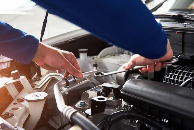 Mãos do mecânico de automóveis com chave na garagem
