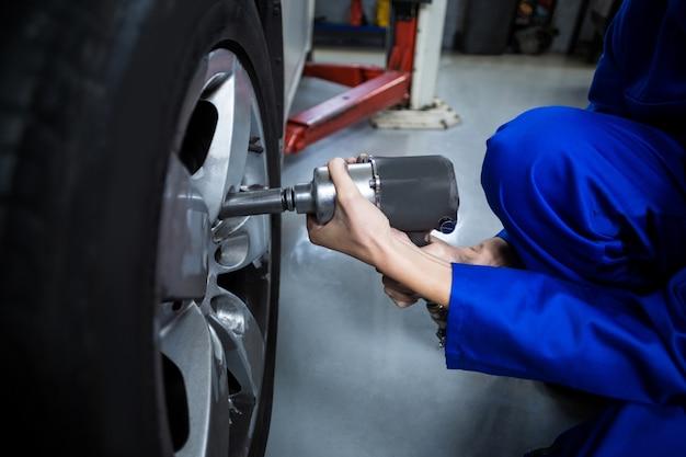 Mãos do mecânico fêmea que fixa uma roda de carro com chave pneumática