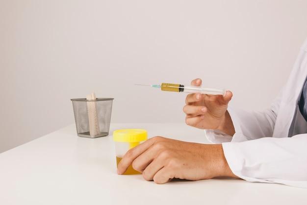 Mãos do médico com teste de urina e seringa