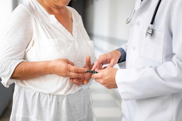 Mãos do médico dando pílulas para paciente