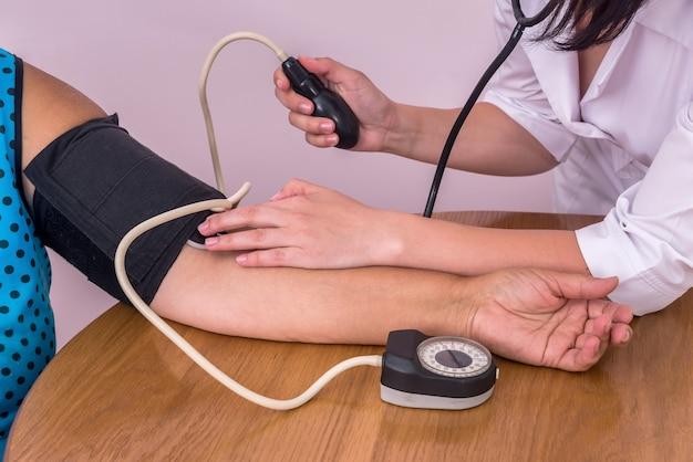 Mãos do médico e do paciente com tonômetro medindo a pressão arterial