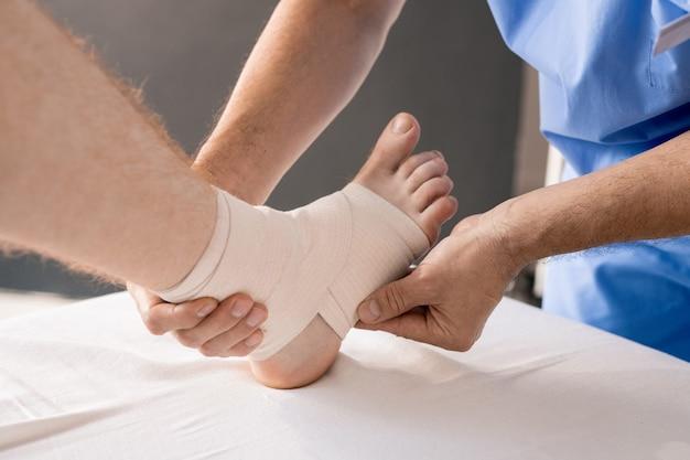Mãos do médico em uniforme envolvendo pé e tornozelo do paciente com bandagem flexível durante procedimento médico no sofá coberto por linho branco