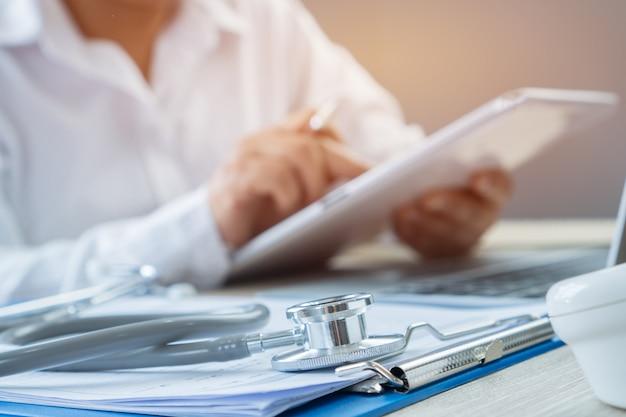 Mãos do médico escrevendo e trabalhando por caneta para medicação de ordem no tablet
