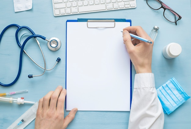 Mãos do médico escrevendo uma prescrição ou relatório médico em uma folha de papel em branco.