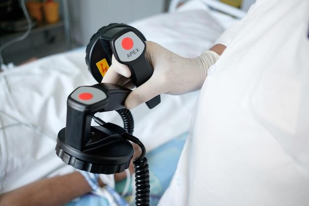 Mãos do médico segurando os eletrodos do desfibrilador, prontos para terapia de desfibrilação ou eletropulsão