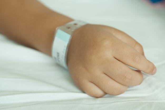 Mãos do menino e do código de barras wristband na cama do hospital