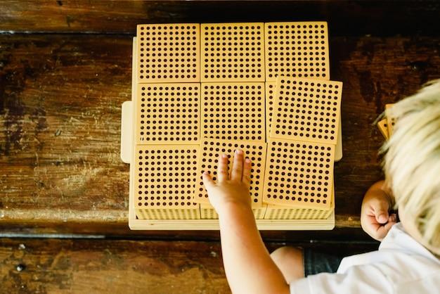 Mãos do menino que manipulam contando cubos no fundo de madeira na sala de aula montessori