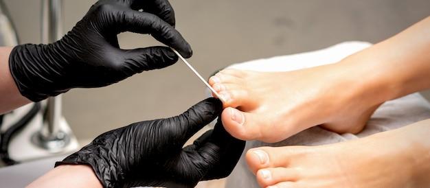 Mãos do mestre de pedicure com luvas protetoras de borracha lixam as unhas dos pés femininos com uma lima em um salão de beleza