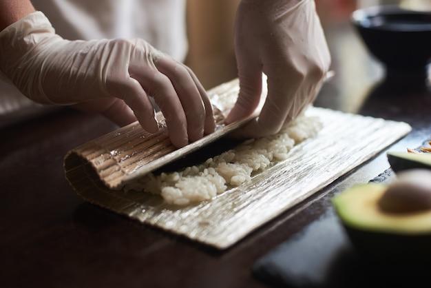 Mãos do mestre fazendo sushi roll com nori, arroz, pepino e omelete usando esteira de bambu