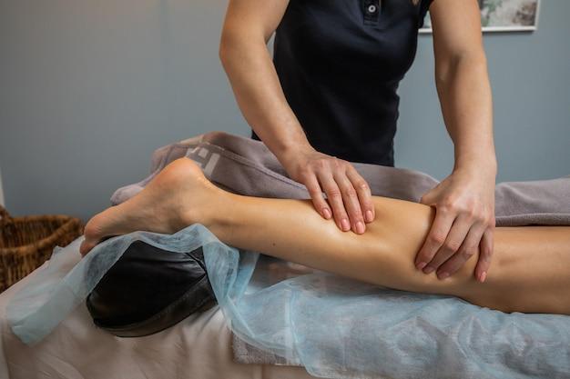 Mãos do mestre massagista feminino faz relaxante massagem nas pernas para jovem mulher close-up. o massagista amassa o músculo da panturrilha do cliente