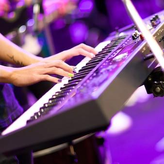 Mãos do músico tocando teclado em concerto com profundidade de campo rasa, foco na mão direita