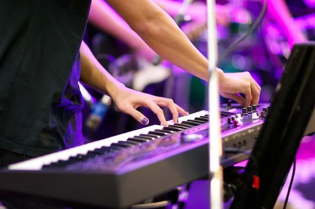 Mãos do músico tocando teclado em concerto com profundidade de campo rasa, foco na mão esquerda