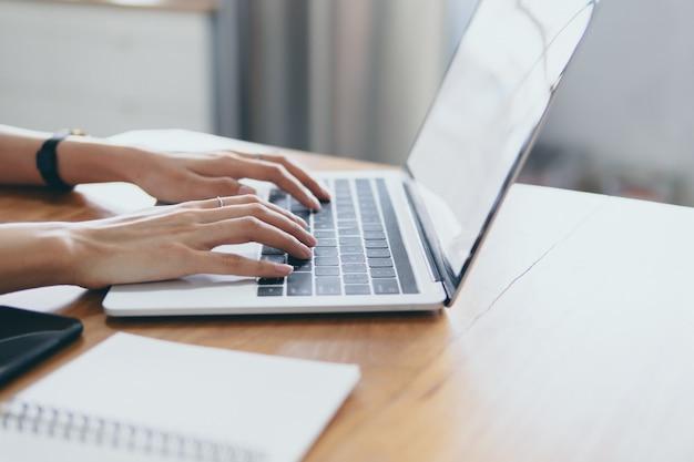 Mãos do negócio que trabalham no laptop durante o processo de trabalho na mesa de escritório.