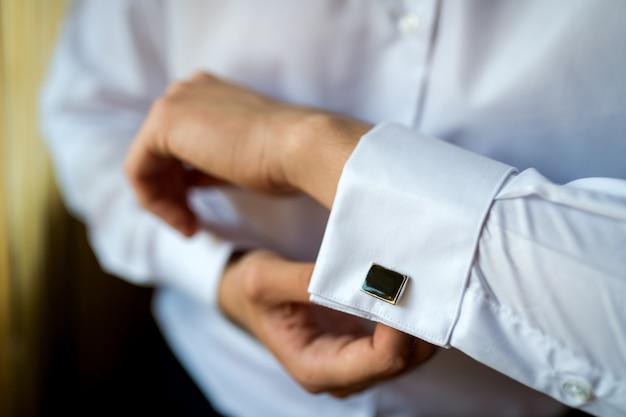 Mãos do noivo do casamento, abotoando sua camisa branca.