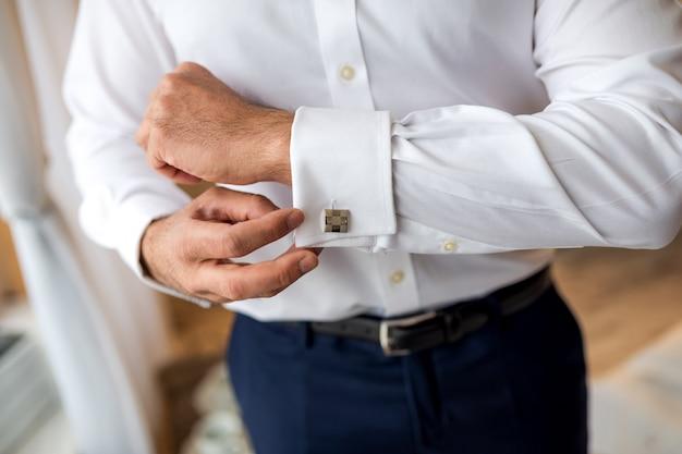 Mãos do noivo do casamento que prepara-se no terno. homem se preparando para o trabalho.