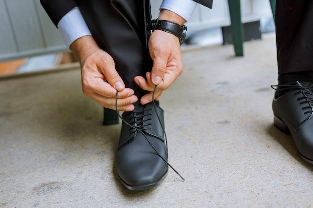 Mãos do noivo do casamento que prepara-se no terno que põe suas sapatas do casamento.