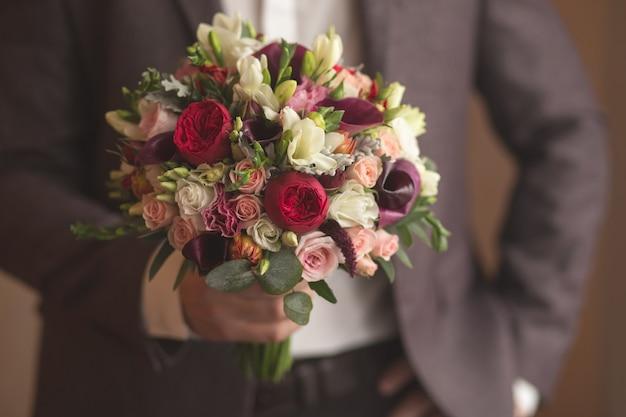 Mãos do noivo do casamento que prepara-se no terno.