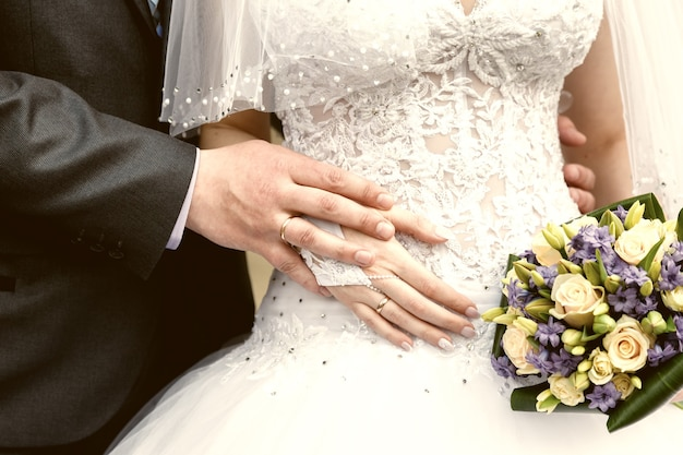 Mãos do noivo e da noiva closeup e buquê de noiva