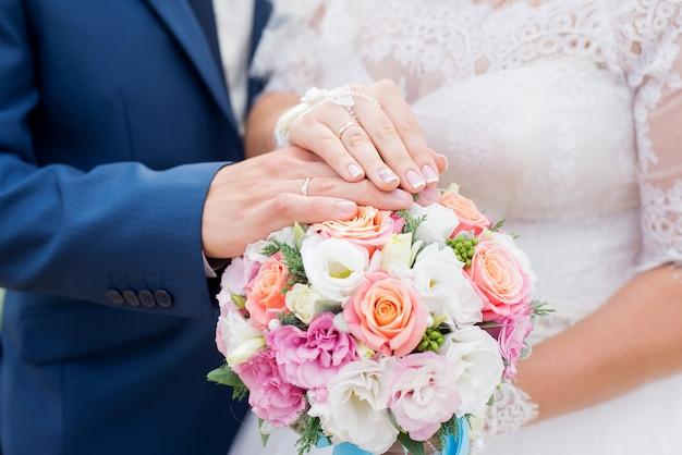 Mãos do noivo e da noiva com anéis de casamento e buquê de flores