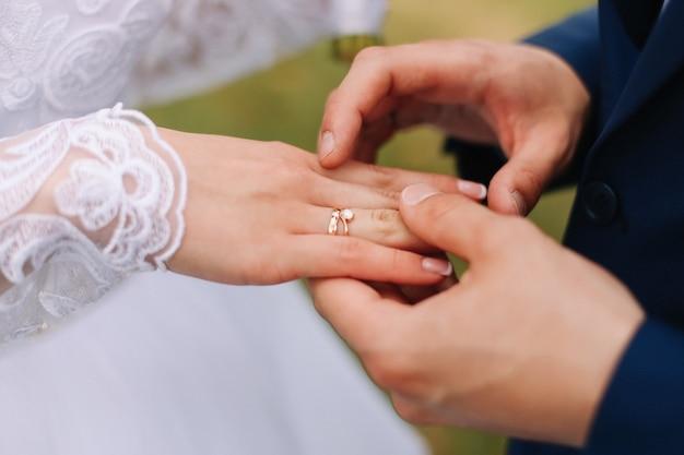 Mãos do noivo e da noiva com anéis de casamento