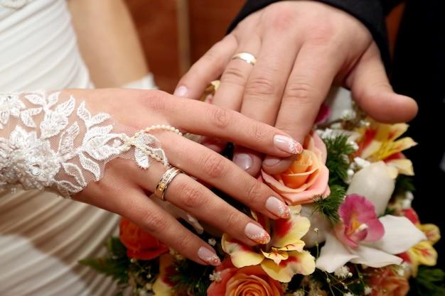 Mãos do noivo e da noiva sobre o buquê