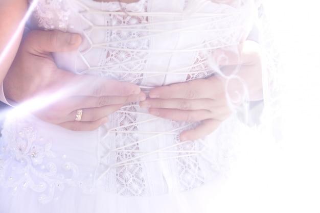 Mãos do noivo na parte de trás da noiva através do véu