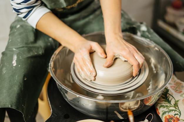 Mãos do oleiro fazendo panela de barro na roda de oleiro