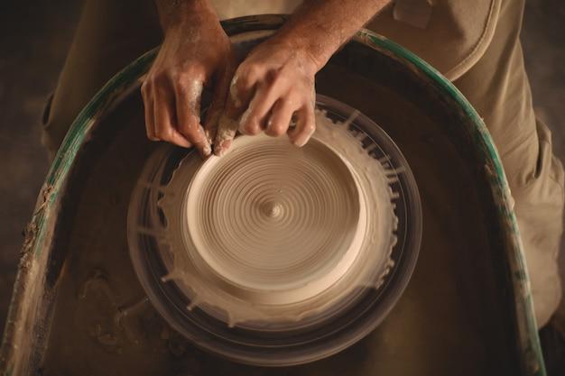 Mãos do oleiro fazendo um pote