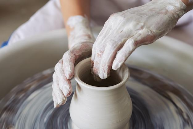 Mãos do oleiro feminino irreconhecível, fazendo o vaso de barro na roda de arremesso