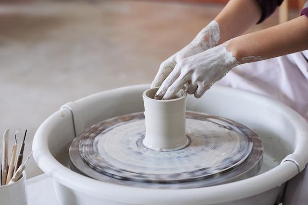 Mãos do oleiro feminino irreconhecível, fazendo o vaso de barro na roda de oleiro