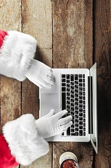 Mãos do papai noel digitando no laptop na mesa de madeira, close-up