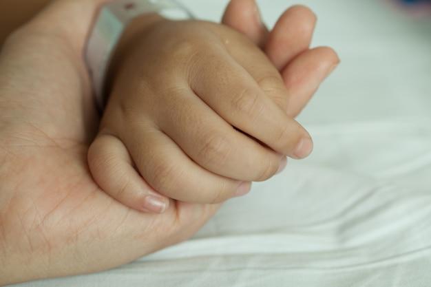 Mãos do pequeno menino e mãos da mãe, código de barras de pulso na cama do hospital