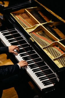Mãos do pianista clássico que jogam seu piano durante um concerto.