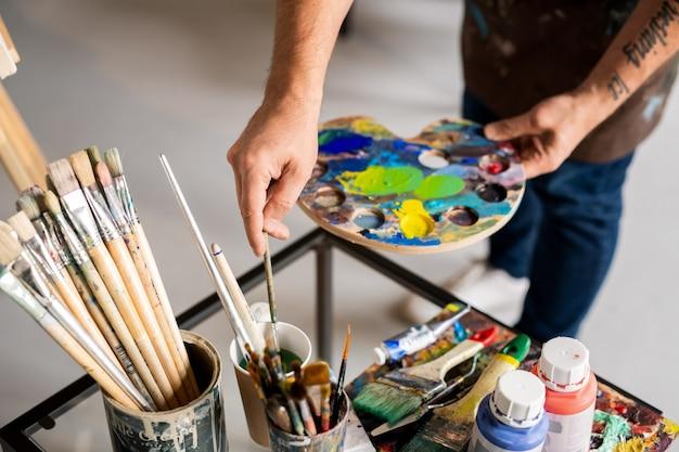 Mãos do pintor segurando paleta com cores misturadas e colocando o pincel no copo d'água durante o trabalho