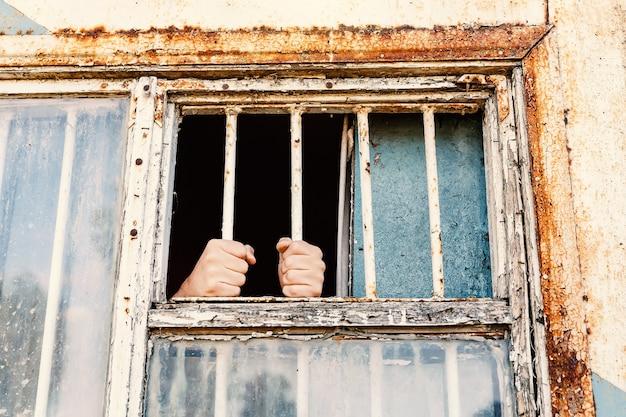 Mãos do prisioneiro em uma treliça de aço.